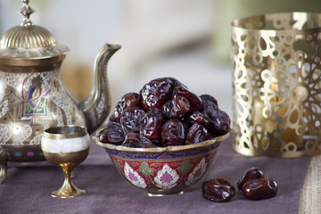 Close-up of fresh dates in ornamental bowl with kettle and cup on a tablecloth