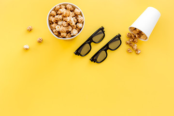 Snacks for film watching in the cinema. Popcorn and soda near glasses on yellow background top view copyspace