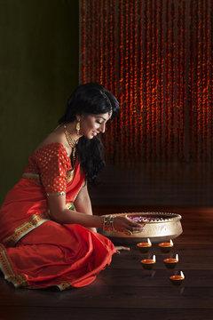 Woman arranging diyas