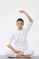 Portrait of young beautiful woman practicing yoga over white background