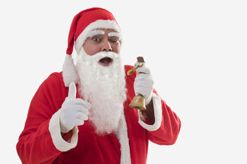 Front view of Santa Claus showing thumbs up while eating chocolate bar over white background