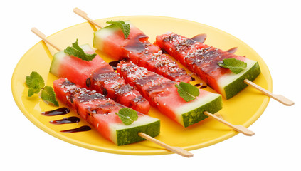 Slices of watermelon with stick on yellow plate isolated on white background. It looks like ice cream. Decorated with mint leaves, coconut and chocolate syrup.