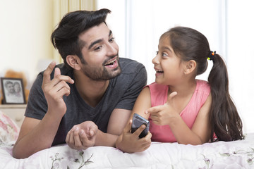 Father and daughter using mobile phone on bed