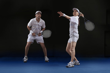 Male and female players playing tennis doubles at court