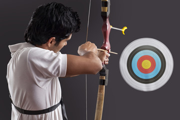 Young man aiming target with bow against black background