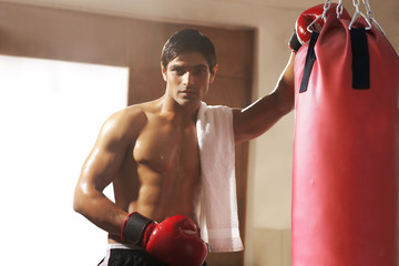 Portrait of young male boxer by punching bag at gym