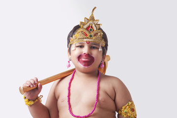 Portrait of cute boy dressed as God Hanuman against white background