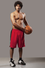 Basket ball player standing over grey background