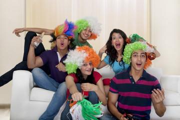 Friends watching a cricket match on tv