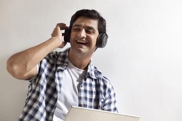 Handsome man using laptop , wearing headphones