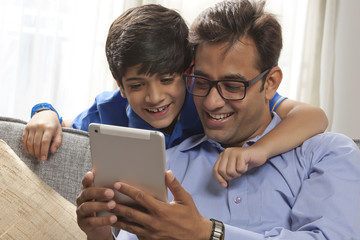 Smiling father using digital tablet sitting on sofa while his son looks from behind