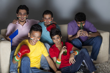 Young male friends watching boxing match together at home