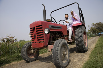 Low angle view of an Indian couple sitting in a tractor