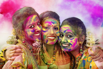 Portrait Of Three Young Indian Women With Colored Face During Holi Color festival