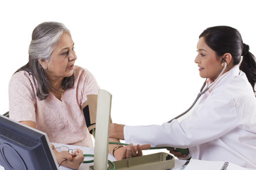 Mid adult doctor checking patient's blood pressure