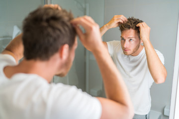 Hair loss man looking in bathroom mirror putting wax touching his hair styling or checking for hair loss problem. Male problem of losing hairs. Fotobehang