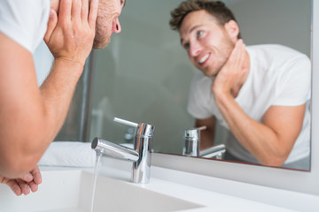 Man washing face in sink in bathroom rinsing after shaving. Home lifestyle copyspace.