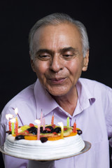 Man blowing out candles on birthday cake