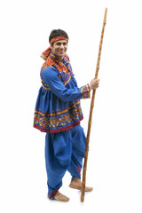 Full length portrait of happy young man in traditional wear holding stick isolated over white background