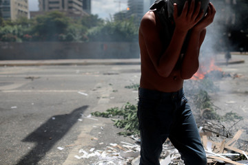 A demonstrator walks past a roadblock at a rally against Venezuela's President Nicolas Maduro's government in Caracas