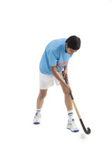 Young male Indian player playing hockey isolated over white background