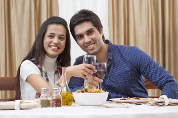 Portrait of a happy young couple having wine at restaurant