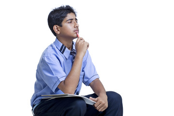 Thoughtful student studying over white background