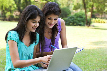 Smiling young women taking notes from laptop