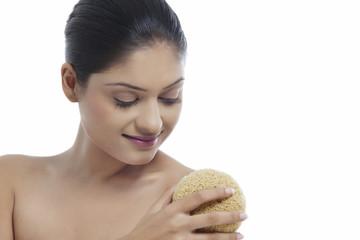 Young woman using massage sponge
