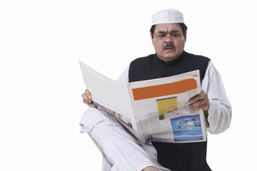 Politician reading newspaper with shocked expression