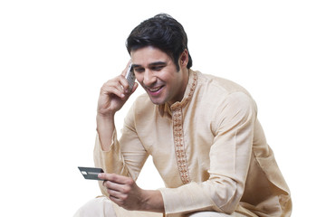 Bengali man paying by credit card on mobile phone