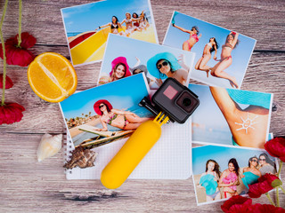 A lot of pictures of young girls in a swimsuit and hats on the sea and an action camera gopro on a wooden table.