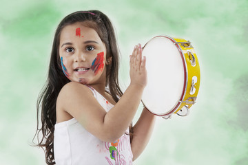 Girl playing on a tambourine