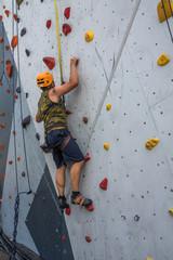 Kletterwand outdoor - Mann klettert angeseilt nach oben