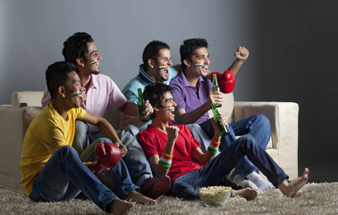 Excited male friends watching boxing match together at home