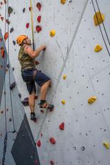 Mann klettert auf Kletterwand mit Griffen - Bergsteigen üben