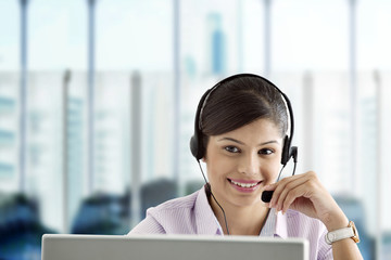 Smiling businesswoman wearing headset and using laptop in office