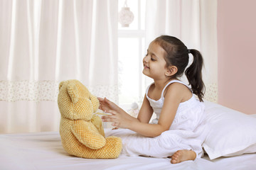 Cute girl playing with teddy bear