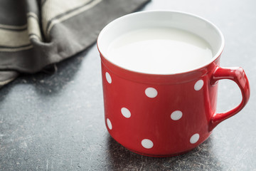 Milk in red mug with white spots.