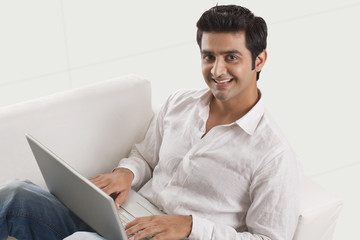 Relaxed young man on sofa using laptop