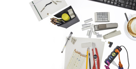 Office supplies and gadgets on white desktop shot directly above