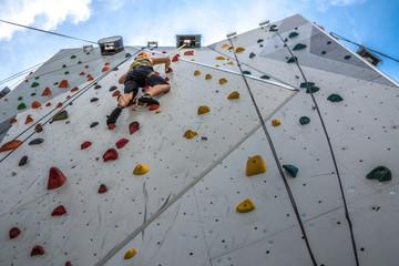 Mann klettert angeseilt auf Kletterwand - Bergsteigen üben