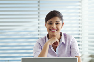 Portrait of smiling businesswoman with laptop at office