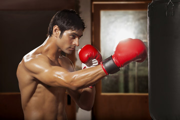 Young shirtless boxer working out with black punching bag in gym