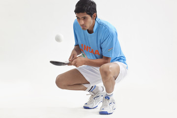 Full length of an Indian man practicing hockey isolated over white background