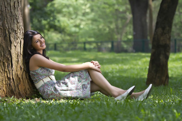 Young woman smiling while leaning against a tree