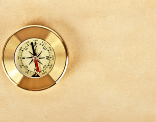 Brown paper and gold compass on a white background