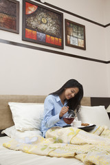 Young woman having morning tea in bed