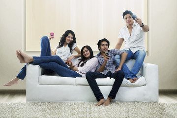 Youngsters with mobile phones sitting on a sofa