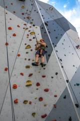 Mann seilt sich ab auf Kletterwand outdoor